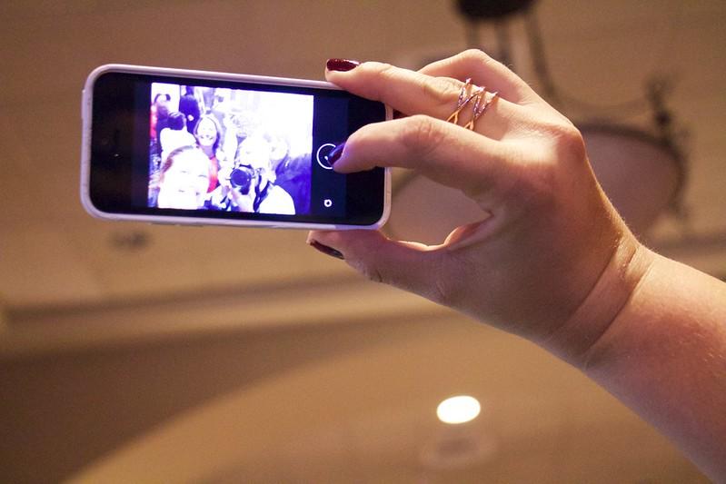 Hand die ein Smartphone hält und gerade ein Selfie schießt mit nicht erkennbaren Gesichtern.